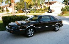 My customized 1989 Chrysler LeBaron GTC Coupe in Black Walnut over Dark Pewter with 2002 PT Cruiser Wheels.